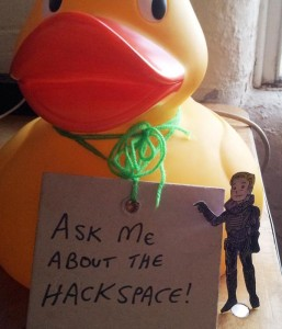 David 8 touches Ein the Duck's sign, which says Ask Me About The Hackspace
