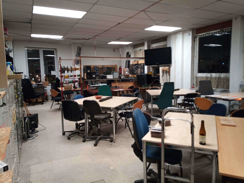 Photo of Hackerspace Brussels' main room featuring tables, chairs and an electronics workspace at the far end.