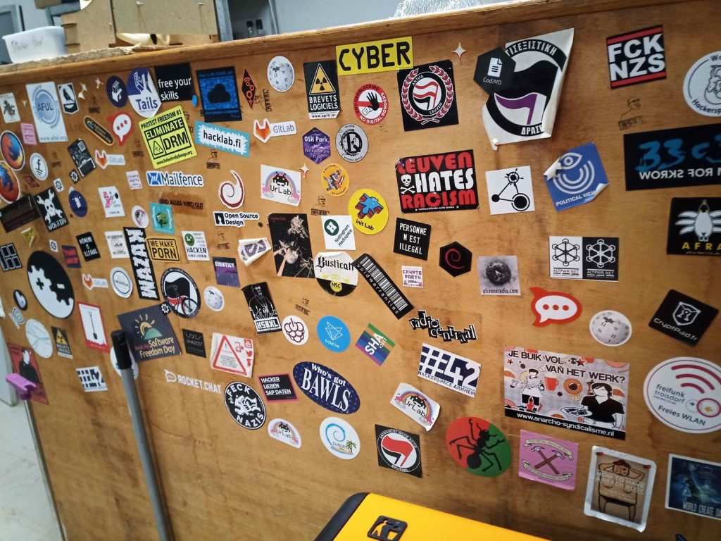 Picture of the wooden 'bar' covered in various technology and hacker related stickers.